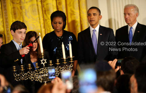 United States President Barack Obama, First Lady Michelle Obama and Vice President Joe Biden watch as Ben Retik lights a candle of the Menorah during a reception for Hanukkah in the East Room of the White House in Washington, DC, Thursday, December 2, 2010.  Hanukkah marks the 8-day Jewish celebration of the Festival of Lights.             .Credit: Mike Theiler - Pool via CNP