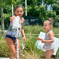 Janelle Jessen/Herald-Leader<br /> Sisters Jocelyn (left) and Evy Bowman of Siloam Springs played in the splash pad at Memorial Park on Sunday. The park and water feature opened in May.