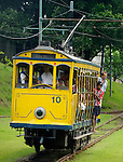 Bonde, Rio's famous electric tram approaching the Terminal dos Bondes in Centro; Rio de Janeiro, Espirito Santo, Brazil. The historic street railway has been transporting Rio residents for over a century. The little yellow tram rattles along the track like an antique roller coaster. Starting from downtown Carioca Station across the Arcos da Lapa (a former aqueduct) it is riding through the neighborhood of Santa Teresa. Seating is on wooden benches, but the local daredevils prefer swinging from the tram's outer poles. --- No releases available.