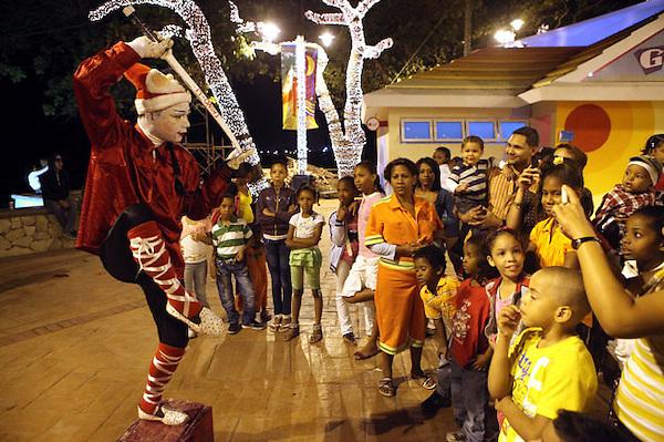 (((SERIE GRÁFICA 7 DE 8))) STO11. SANTO DOMINGO (REPÚBLICA DOMINICANA), 20/12/2011.- Un artista actúa frente a niños este, lunes 19 de diciembre de 2011, en la playa Güibia en Santo Domingo (República Dominicana). EFE/ORLANDO BARRÍA.
