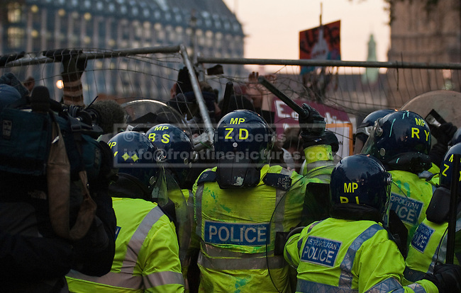 Demonstrators maneuver fencing taken from Parliament Square before attempting to use it as barrier to push back police lines during the fourth protest against tripling of tuition fees in England and Wales. 09/12/10