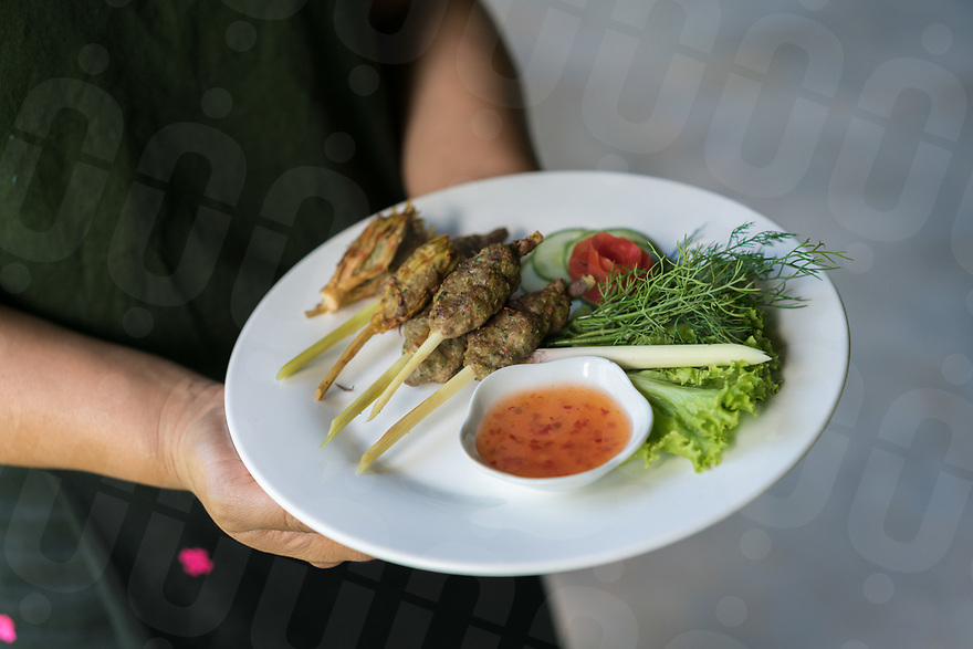 May 13, 2017 - Luang Prabang (Laos). Chef Sing Sondar poses for a portrait handling a plate of lemongrass stuffed with pork and herbs. © Thomas Cristofoletti / Ruom
