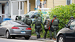 WATERBURY,  CT-051719JS11-  Waterbury police prepare to enter a home on East Liberty Street on Friday as part of a city-wide operation. Waterbury Police, with cooperations State Police, Watertown Police, the States Attorney's Office, the DEA and ATF, conducted search and seizures as well as searching for wanted suspects who police say were suspected in the sale of heroin.<br /> Jim Shannon Republican American