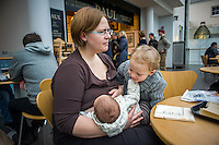 A mother breastfeeding her baby  in a museum cafe while the older sybling tries to play with the baby.<br /> <br /> London, England, UK<br /> 08/03/2015<br /> <br /> &copy; Paul Carter / wdiip.co.uk