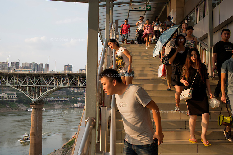 People walk down stairs to an elevated subway platform at the Niujiaotuo subway station in the Yuzhong district of Chongqing, China. Visible at left is the Chongqing Jialingjiang Bridge over the Jialing River.