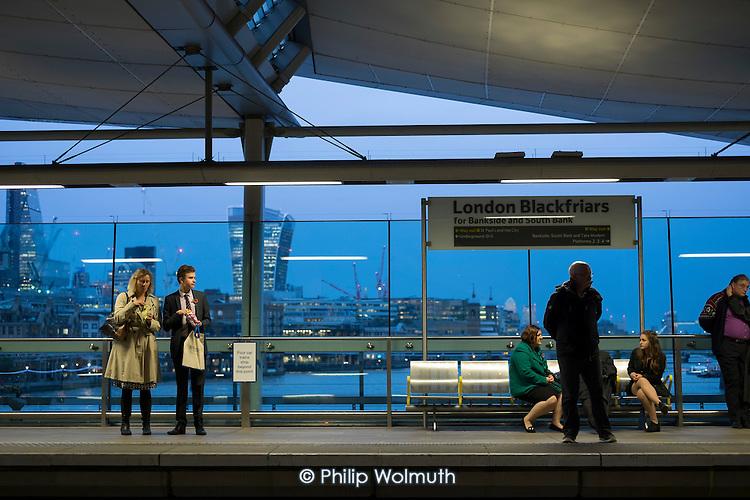 Passengers on London Blackfriars station platform, and City of London at dusk.