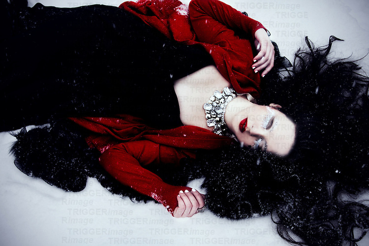 A pale girl with long black hair wearing a black gown lying in the snow with eyes closed.