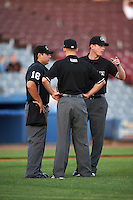 Umpire Ryan Wills (right) confers with home plate umpire Jorge Teran (left) and third base umpire Ben Levin (center) on a call during the second game of a doubleheader between the Trenton Thunder and Hartford Yard Goats on June 1, 2016 at Sen. Thomas J. Dodd Memorial Stadium in Norwich, Connecticut.  Trenton defeated Hartford 2-1.  (Mike Janes/Four Seam Images)