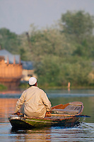 Man paddling a traditional Kashmiri shikara, or gondola, at sunrise, Dal Lake, Srinagar, Kashmir, India..