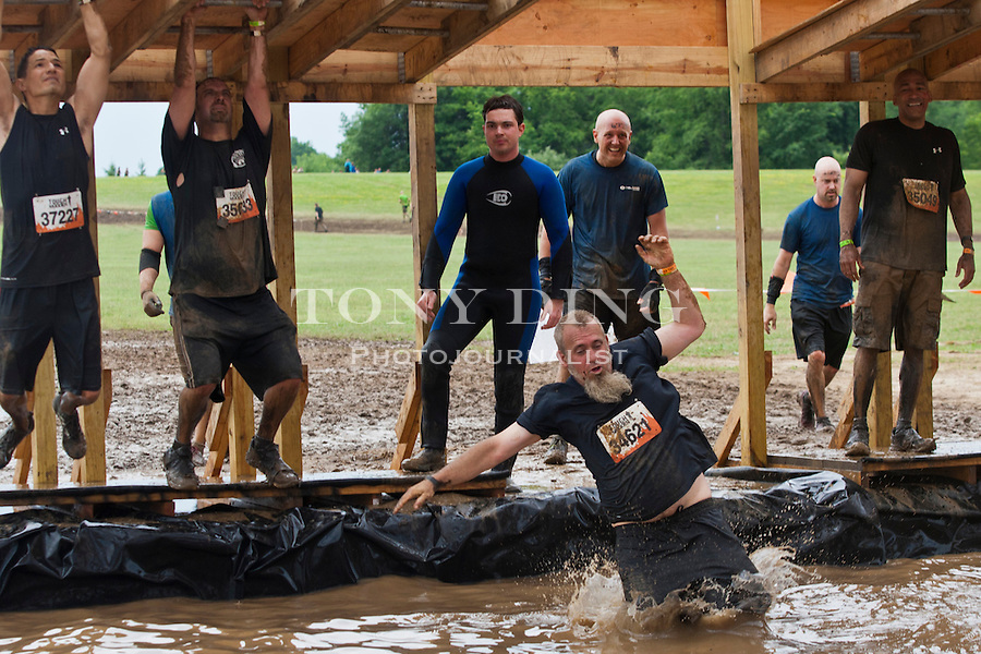 "16 April 2010: Competitors climbs through the ""Funky Monkey"", one of twenty obstacles in the Tough Mudder adventure endurance race at Michigan International Speedway in Brooklyn, Michigan."