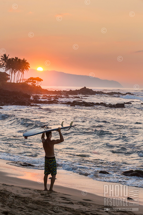 A surfer watches the sunset at the beach after surfing, North Shore, O'ahu.