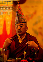 Buddhist  head priest conducting a prayer ceremony inside a monastery in Sikkim India