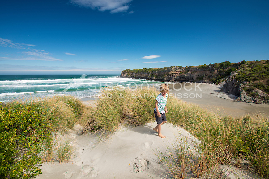 Young boy playing in the sand dunes at Tomahawk Beach on a sunny blue sky day, Dunedin, Otago, South Island, New Zealand - stock photo, canvas, fine art print