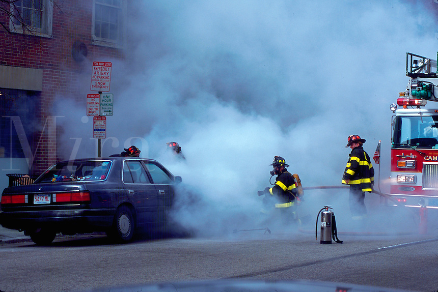 Firemen putting out a car fire