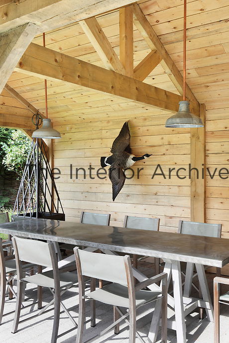 An outdoor dining area complete with metal pendant lights and a large dining table and chairs