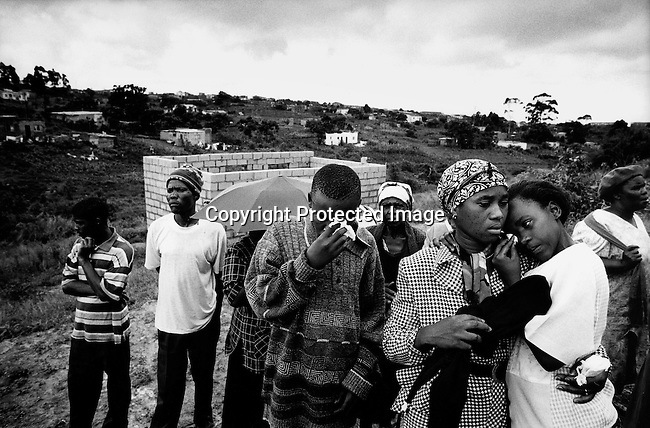 Relatives attend a funeral for a woman who died of an Aids related disease on September 13, 1999 in Gamalakhe, in Natal, South Africa. South Coast Hospice, a local hospice that helps people in this rural area, helped the family to pay for the funeral. It's estimated that about one thousand South African's die every day and that about 5.5 million of the population are infected. (Photo by: Per-Anders Pettersson)..