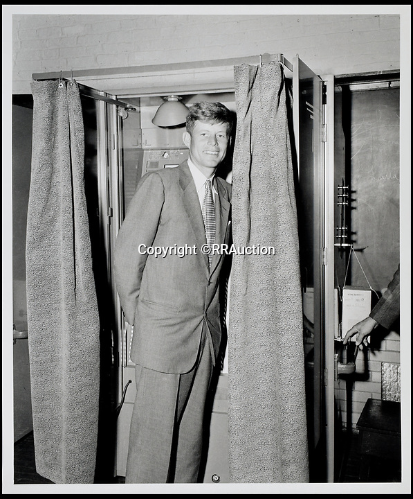 BNPS.co.uk (01202 558833)<br /> Pic: RRAuction/BNPS<br /> <br /> JFK proudly standing in front of a Boston voting booth on election day in 1952 getting ready to cast his vote for himself at the conclusion of the 1952 senatorial campaign which JFK would win.<br /> <br /> Incredibly-rare photos highlighting the first foray into politics for John F. Kennedy that would eventually cost him his life have come to light.<br /> <br /> The 100 black and white snaps show a youthful-looking JFK from 1946, when he was campaigning to become a US congressman for the first time.<br /> <br /> The tragic future president is seen during an oration lesson where he was given help by an expert with public speaking and posture.<br /> <br /> The 29-year-old is also depicted mingling with the public at an annual parade and as well as celebrating his first political victory - a congressional primary vote - in June 1946.<br /> <br /> The images are being sold by US-based RR Auction.