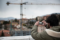 L'aquila, Abruzzo, Italia. 25.03.2014. Pietro Verga studerer ved Gran Sasso Science Institute. Han dokumenterer daglig fremgagen i rekonstruksjonen av byen fra nøyaktig samme sted på taket av skolen. L'aquila, 6. april 2009 kl. 03:32: Et jordskjelv som måler 6.3 ryster byen. 309 mennesker mister livet. Fem år senere sliter de som overlevde fortsatt med etterskjelvene, i form av en guffen cocktail av uærlige offentlige tjenestemenn, mafia og 494 millioner øremerkede euro på avveie. Fotografier til bruk i feature i DN lørdag 05.04.2014. Foto: Christopher Olssøn.