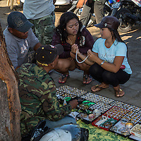 Jimbaran, Bali, Indonesia.  Customers Examine Vendor's Selection of Rings and Necklaces.