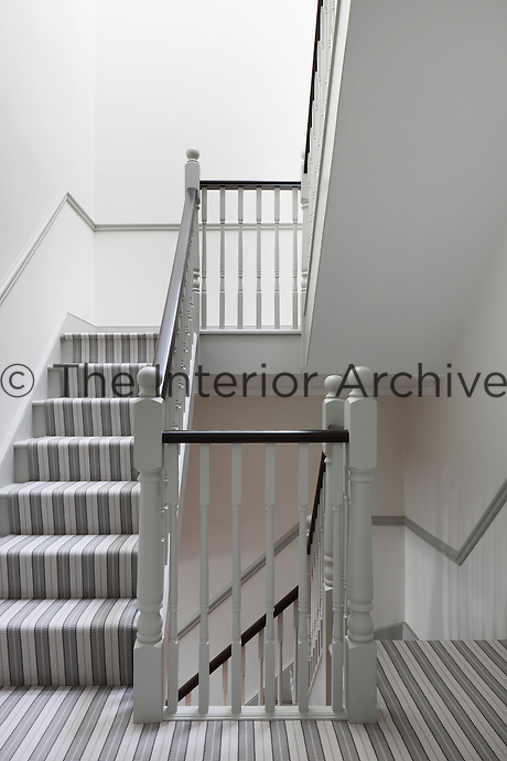 A pale grey stairwell with grey and white striped carpet