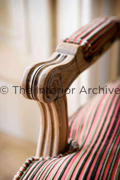 Close-up of wooden arm on red upholstered bench