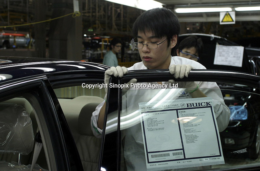 A Chinese worker inspects a door of a newly built Buick Regal at the Shanghai General Motors (SGM) plant in Shanghai, China. SGM is a joint-venture between General Motors and the Shanghai Automotive Industry Corporation also known as SAIC..