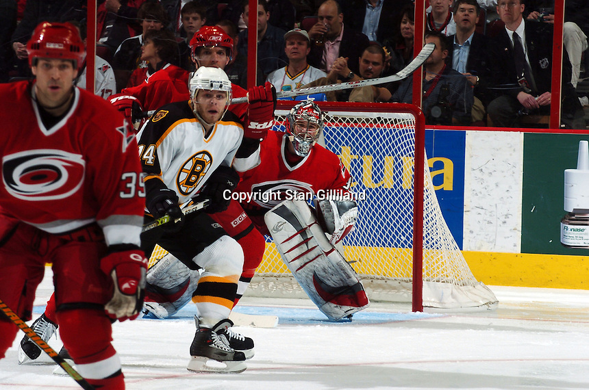 The Boston Bruins' Sergei Samsonov (14) of Russia, looks for the puck while defended by the Carolina Hurricanes' Doug Weight, far left, Bret Hedican, behind, and goaltender Cam Ward during their game at the RBC Center in Raleigh, NC Wednesday, March 1, 2006. The Hurricanes won 4-3...