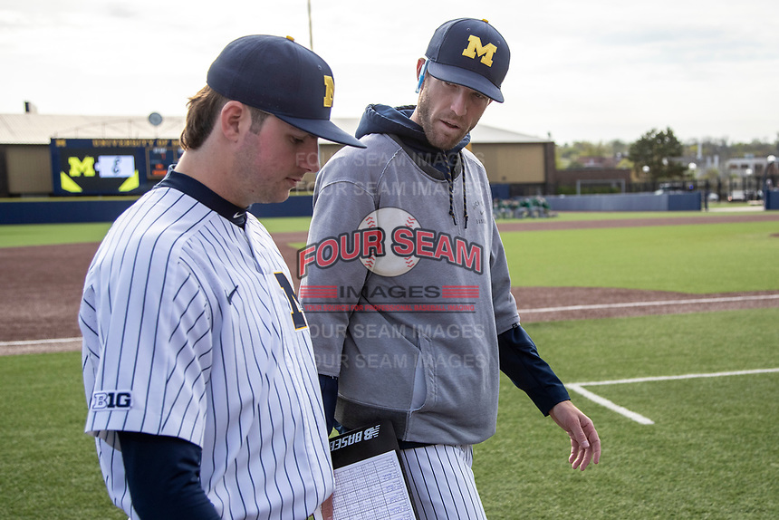 Michigan Wolverines pitching coach Chris Fetter talks with Jeff Criswell (17) before theNCAA baseball game against the Eastern Michigan Eagles on May 8, 2019 at Ray Fisher Stadium in Ann Arbor, Michigan. Michigan defeated Eastern Michigan 10-1. (Andrew Woolley/Four Seam Images)