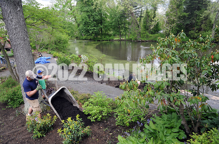 Nick Primola of Yardley, Pennsylvania drops a wheelbarrow full of mulch during a community cleanup of Lake Afton to provide some relief for the algae-plagued and mucky man made lake Saturday, May 6, 2017 at Lake Afton in Yardley, Pennsylvania. (WILLIAM THOMAS CAIN / For The Philadelphia Inquirer)