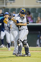 Asheville Tourists catcher Wilfredo Rodriguez (3) hugs relief pitcher Jefri Hernandez (30) following their win over the Kannapolis Intimidators at CMC-NorthEast Stadium on July 12, 2014 in Kannapolis, North Carolina.  The Tourists defeated the Intimidators 7-5 in 15 innings.  (Brian Westerholt/Four Seam Images)