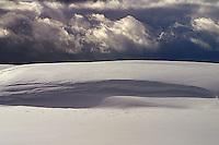 Winter in Hayden Valley is time of both wind and deep snow.  Cornices form and solidify. Here there are tracks across the face just as the storm moves in.