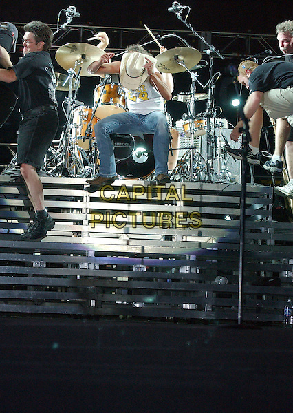 KENNY CHESNEY.The Road and The Radio Tour 2006 held at Crew Stadium, Columbus, Ohio, USA, 27 May 2006..full length cowboy hat country music concert gig live on stage funny sitting hat over face drums drummer.Ref: ADM/LF.www.capitalpictures.com.sales@capitalpictures.com.©Laura Farr/AdMedia/Capital Pictures.