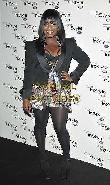 "Misha ""Misha B"" Bryan.The InStyle magazine 10th anniversary party, Sanctum Soho hotel, Warwick St., London, England..November 22nd, 2011.full length black blazer jacket dress tights white print goody bag hand on hip.CAP/CAN.©Can Nguyen/Capital Pictures."
