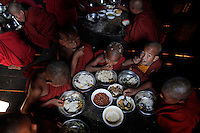 Buddhist novice monks eat at a temple where local villagers meet UNODC and Myanmar's police representatives in the village of Kyauk Ka Char in mountains of Shan State January 26, 2012. Myanmar has dramatically escalated its poppy eradication efforts since September 2011, threatening the livelihoods of impoverished farmers who depend upon opium as a cash crop to buy food. With new ceasefires ending years of conflict between the government and ethnic insurgents, Myanmar police and United Nations officials travel through opium-rich Shan State to ask farmers what assistance they need.   REUTERS/Damir Sagolj (MYANMAR)