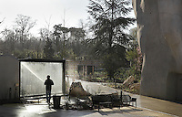 Member of staff hosing down a viewing window of the Guinea baboon enclosure, with the Rocher de Garde and the Zone Sahel-Soudan on the right, in the new Parc Zoologique de Paris or Zoo de Vincennes, (Zoological Gardens of Paris or Vincennes Zoo), which reopened April 2014, part of the Musee National d'Histoire Naturelle (National Museum of Natural History), 12th arrondissement, Paris, France. Picture by Manuel Cohen