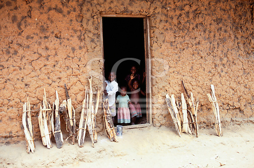 Ujiji, Tanzania. Small bundles of fuelwood leaning against the mud wall of a house with small children in the doorway.