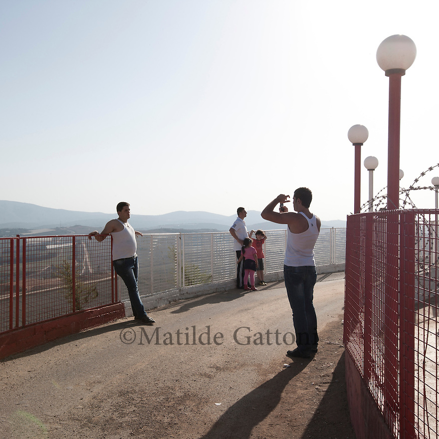 Lebanese ftaking each other's pictures in the park overlooking Israel. During his first state visit to Lebanon in October 2010  Iranian President Dr. Ahmadinejad went to Bint Jbeil, a village at Israel-Lebanon border. Its the place where fierce battles between Hizbullah and the Jewish Army were fought. In addition to praising the courage of the Lebanese nation against the powerful enemy supported by the US, France, Germany and Britain  Dr. ahmadinejad also performed the inauguration ceremony of the Iran Park at Maroun al-Ras border area where streets are named after the Iranian cities...The Iranian government has funded and designed a lush park near the site of the battle, on the mountainside directly overlooking Israel. In the parking, visitors can stand at an observation point beside an Iranian flag fluttering in the wind, and look directly down at the Israeli hamlets of Avivim and Yiron.