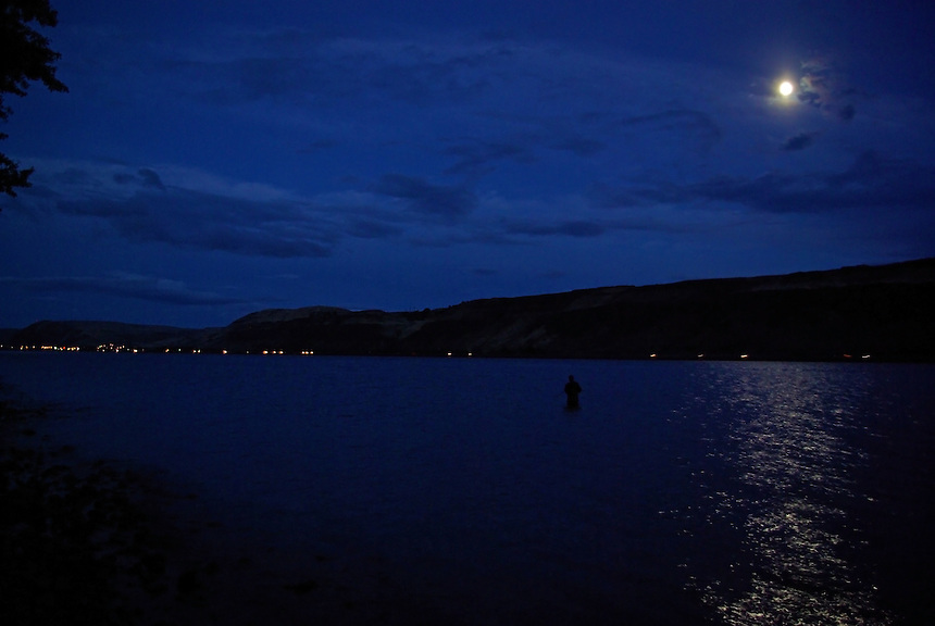 Man wade fishing at night on Columbia River in Oregon