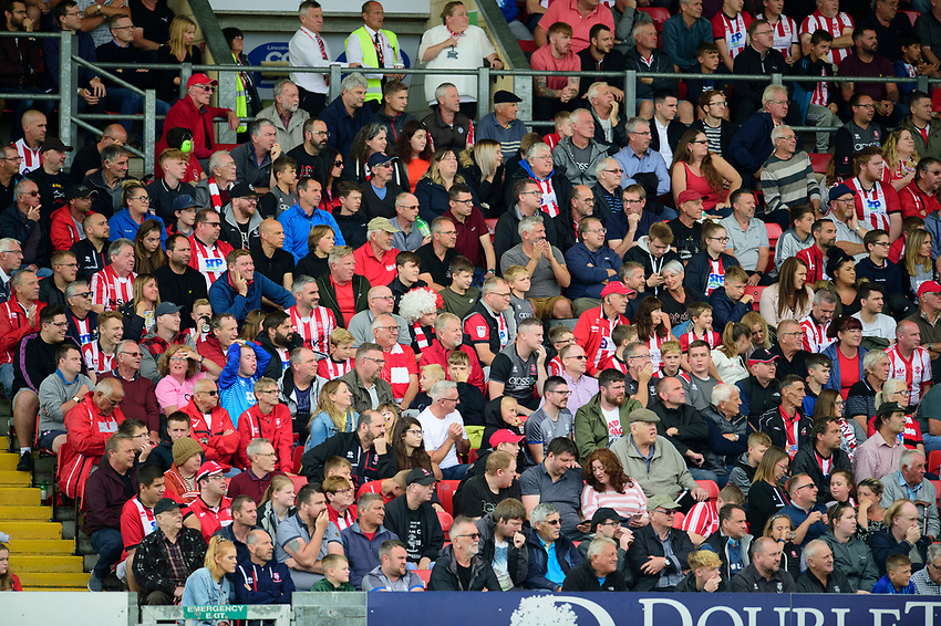 Lincoln City fans watch their team in action<br /> <br /> Photographer Andrew Vaughan/CameraSport<br /> <br /> The EFL Sky Bet League One - Lincoln City v Fleetwood Town - Saturday 31st August 2019 - Sincil Bank - Lincoln<br /> <br /> World Copyright © 2019 CameraSport. All rights reserved. 43 Linden Ave. Countesthorpe. Leicester. England. LE8 5PG - Tel: +44 (0) 116 277 4147 - admin@camerasport.com - www.camerasport.com