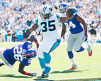 The Carolina Panthers played the New York Giants at Bank of America Stadium in Charlotte, NC.  The Panthers won 38-0 for their first victory of the season.  The Giants dropped to 0-3.  Carolina Panthers fullback Mike Tolbert (35) runs for a touchdown evading New York Giants strong safety Antrel Rolle (26)