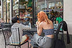 Two people eating at an outdoor café in Harvard Square