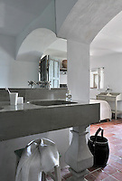 A simple bedroom with a stone wash basin ensuite has windows opening onto a fabulous view of the Mediterannean