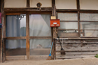 The door of a house in the abandoned village of Tsushima in rural Fukushima near the exclusion zone, Fukushima Japan. Wednesday May 5th 2011. A 20 kilometre exclusion zone was set up on April 22nd to limit exposure to radiation from the Fukushima Daichi nuclear power station that was damaged in the earthquake and tsunami of March 11th 2011