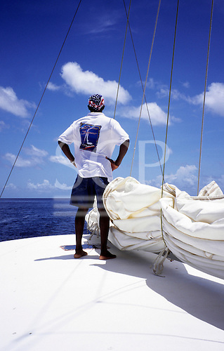 St. Lucia. Man with denim shorts, white t-shirt with large logo and stars and stripes bandana on boat.