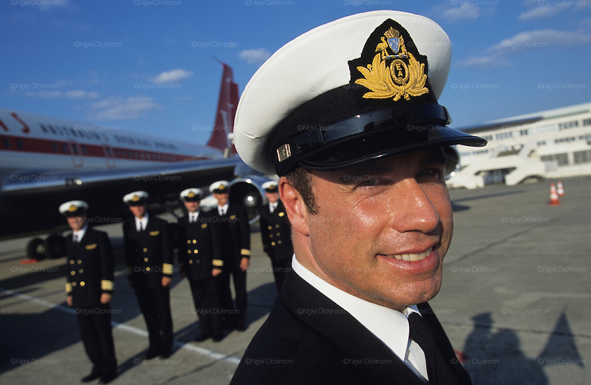 "John Travolta, Captain and pilot, of his own jumbo jet, with his plane and crew behind...John Travolta is pilot of his very own jumbo jet, a 1964 Boeing 707-100 series. In 2003, John Travolta flew his jumbo jet around the world, in partnership with Quantas, to rekindle confidence in commercial aviation, and to remind us that elegance and style are a part of flying. The crew are dressed in tailor made authentic uniforms from the Quantas museum. The men's uniforms are styled on British Naval uniforms and the ladies' designed by Chanel. His jumbo jet sports a personalised number plate N707JT which speaks for itself. The aircraft is named ""Jett Clipper Ella"" dedicated to his son and daughter. This jumbo together with his other aircraft are housed in purpose built hangars at his home in Florida, USA."