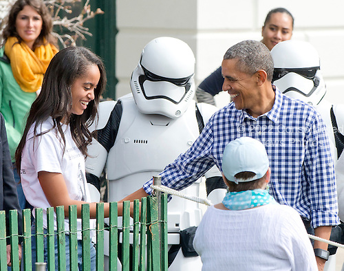 United States President Barack Obama and his daughter Malia  attend the 2016 White House Easter Egg Roll on the South Lawn of the White House in Washington, DC on Monday, March 28, 2016.  A Star Wars storm trooper looks on.<br /> Credit: Ron Sachs / CNP