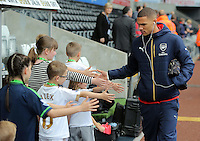 Kieran Gibbs of Arsenal is greeted by children mascots as he arrives prior to the Barclays Premier League match between Swansea City and Arsenal at the Liberty Stadium, Swansea on October 31st 2015