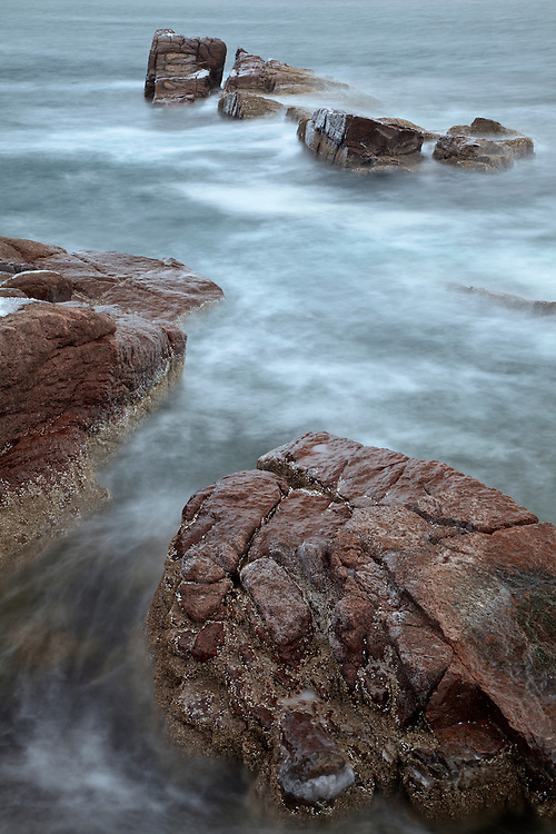 Waters from the Atlantic Ocean move about partially submerged boulders just off shore from Thunder Hole in Acadia National Park, Maine, USA
