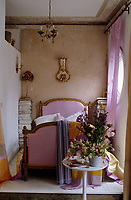 A Louis XVI giltwood bed upholstered in pink silk is flanked by towers of magazines against a raw plaster wall
