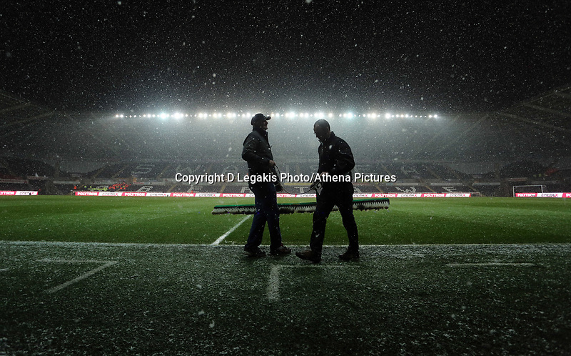 Wednesday 23 January 2013<br /> Pictured: Swansea City FC groundsman Dan Duffy (L) assisted by a colleague are brushing the snow away.<br /> Re: Capital One Cup semi-final second leg, Swansea City FC v Chelsea at the Liberty Stadium, south Wales.